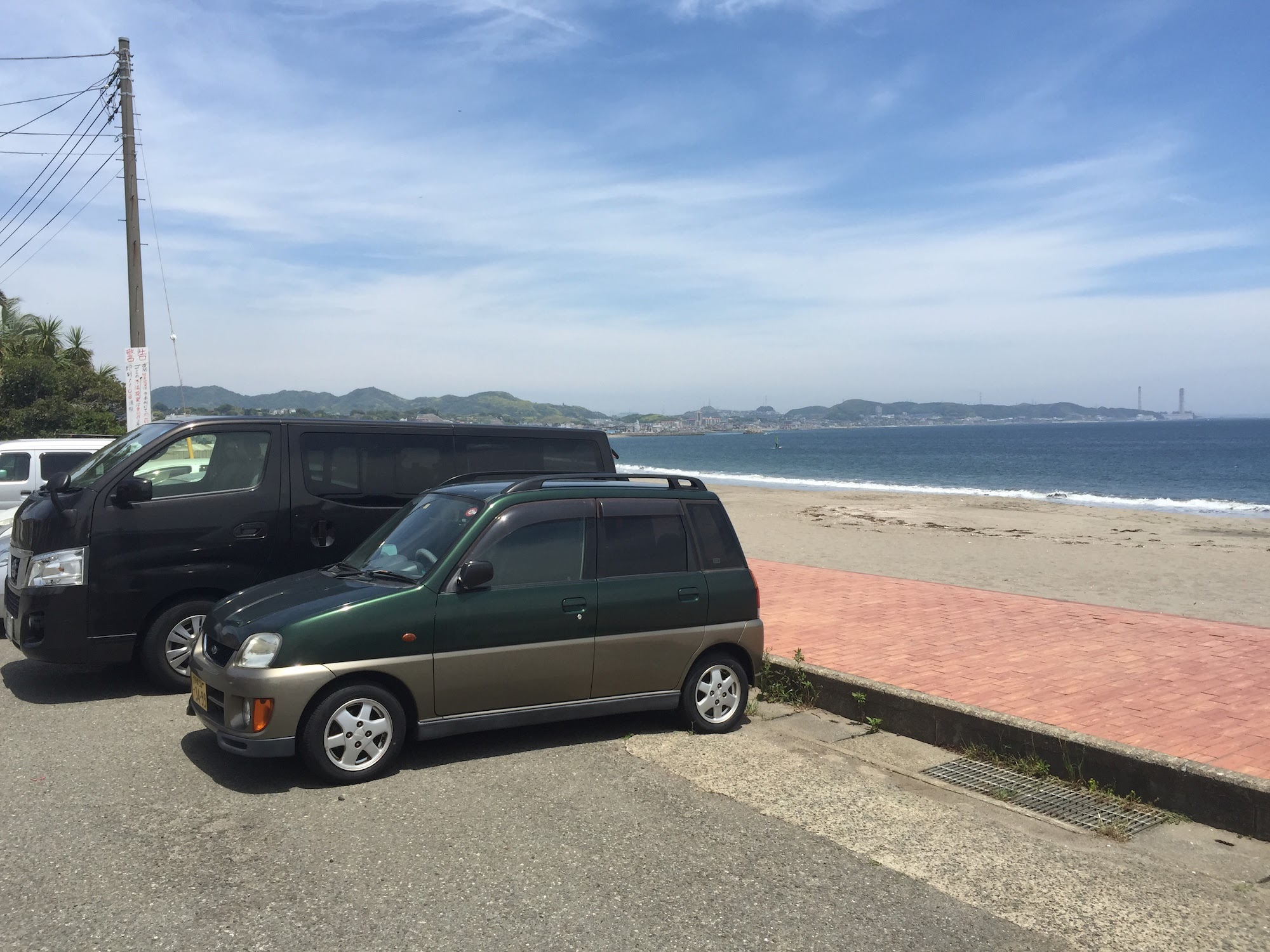 full size van next to a kei car